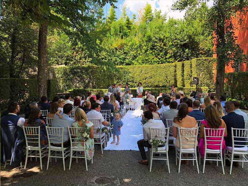 The ceremony area was surrounded by tall trees, providing some relief from the heat.